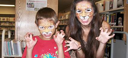 a child and adult with faces painted like leopards